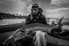 Jamie Dietman holds a 46-inch sturgeon caught on the rainy river
